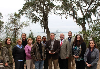Environmental educator Mark Madden holds the trophy he was awarded by winning the 2015 South Carolina Environmental Awareness Award. He is shown on the shore of Charleston Harbor along with some of his colleagues at Charleston County Parks and Recreation Commission, members of the award planning committee and host agency representatives. (SCDNR photo by Erin Weeks)