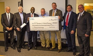 Duke Energy executives present SCDNR officials with a check for $984,800, January 19, 2017 in Columbia. From left to right: Duke Energy Director of Environmental Policy and Affairs, Mike Ruhe, Duke VP for Water Strategy and Hydro Relicensing Steve Jester, Duke State President for S.C. Kodwo Ghartey-Tagoe, Duke Senior Project Manager Mark Oakley, SCDNR Director Alvin Taylor, S.C. Natural Resources Board Chairman Cary L. Chastain and SCDNR Director of Environmental Programs Bob Perry. [SCDNR photo by D. Lucas]