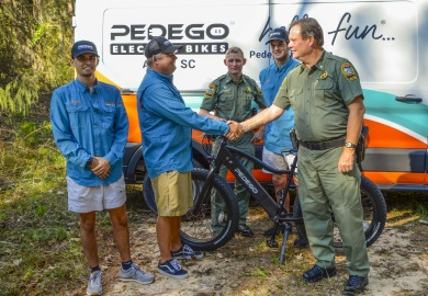 Major Gary Sullivan with the SCDNR shakes hands with Pedego of Aiken owner Coker Day during a day spent testing the new electric bicycle being donated to the agency. Also pictured are Pedego of Aiken Manager Shane LeDonne (far left), SCDNR Lance Corporal Jeff Day (center) and Pedego of Aiken Mechanic Ryan Blane. [SCDNR photo by David Lucas]