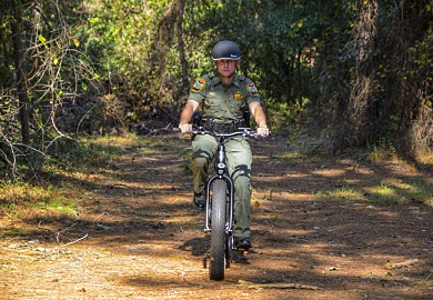 SCDNR Lance Corporal Jeff Day tests the Pedego electric bicycle. [SCDNR photo by David Lucas]