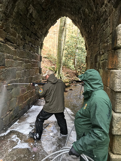 SCDNR Heritage Trust staff (from left) Brian Long and Abel Tobias use a pressure washer to remove graffiti from historic Poinsett Bridge at the heritage preserve in northern Greenville County. (SCDNR photo by Greg Lucas)