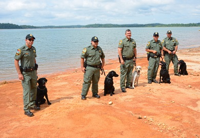 The SCDNR Canine Team, shown here beside Lake Hartwell in Pickens County, will be a key ingredient in SCDNR's law enforcement efforts. From left are Lance Cpl. Brian Welch of Clemson and 'Max'; Pfc. Patrick Nettles of Bamberg and 'Cash'; Capt. Gentry Thames of Pineland and 'Rio'; Pfc. Brian Urquhart of Florence and 'Lola'; and Sgt. Freddie Earhart of Moncks Corner and 'Blue.' (SCDNR photo by Greg Lucas)