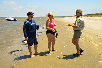 Cape Romain Shorebird Steward Jennifer Cahill talks with visitors on the beach near the southern tip of Lighthouse Island.