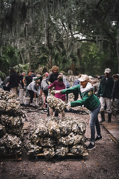 SCORE's Ryan Raiford tosses a bag of recycled oyster shells atop a pile that will be planted on a South Carolina shore later this year. (Photo: Dylan Schmitz)