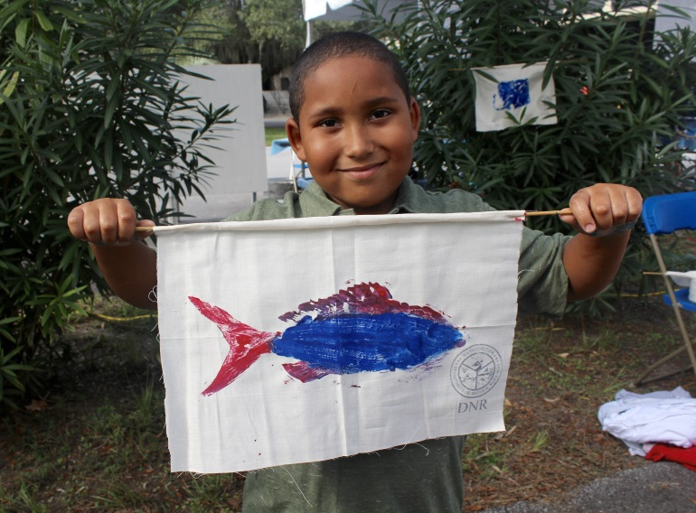 Young boy with hand made fish print artwork